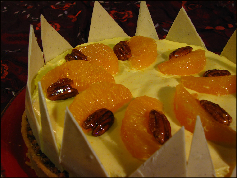A rich and crisp pastry shell filled with pecan nuts in a caramel base gently infused with cinnamon, topped with an impossibly light orange mousse, orange segments and caramelised pecans, surrounded by white chocolate shards.