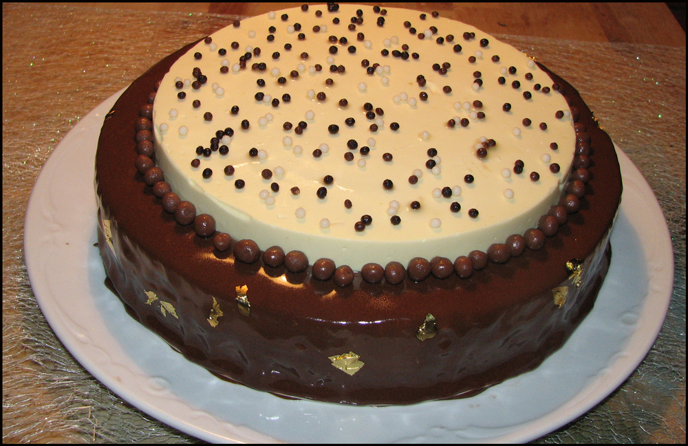 A chocolate crumb sits beneath a sabayon-based, Cointreau-chocolate cheesecake covered in a dark chocolate mirror glaze, topped with a disc of rum mascarpone cream.